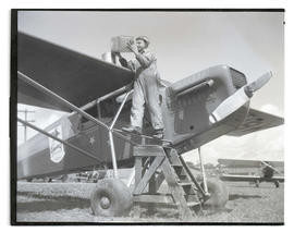 James Rinehart? standing on strut of General Gasoline airplane, filling a can