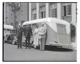 Four people posing  with travel trailer, Southeast 6th and Alder, Portland