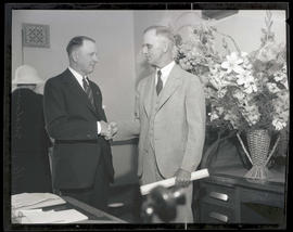 Internal revenue collector Clyde G. Huntley shaking hands with successor James W. Maloney