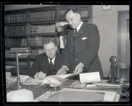 Donough and Newman? at desk, looking at document