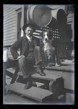 Unidentified man and dog sitting on porch steps