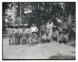 Group of Native American men and children posing near trees