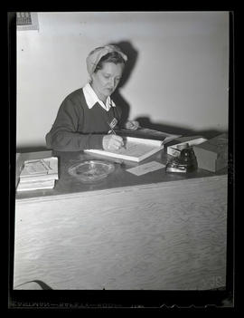 Worker writing in receipt book during swing shift, Albina Engine & Machine Works, Portland