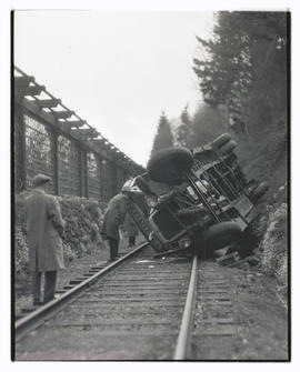 Bus lying on railroad tracks