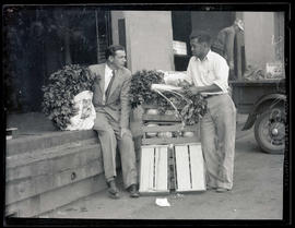 Farmer? and unidentified man outside building, talking and holding vegetables