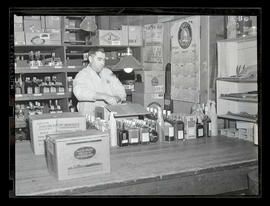 Unidentified man unpacking box of liquor in store or warehouse
