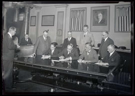 Portland Mayor George L. Baker and three unidentified men signing documents in city council chambers