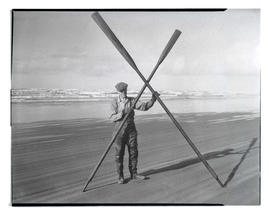 Unidentified man on beach holding crossed oars, one broken