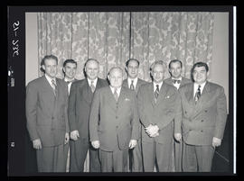 Group of men in front of curtain