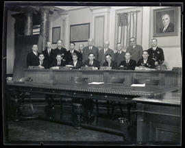Group of men posing in Portland City Council chambers