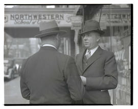 Two unidentified men outside building