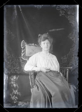 Unidentified woman sitting in rocking chair, three-quarters portrait