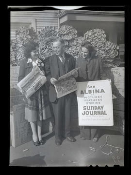 Three unidentified people posing with newspapers and sign at Albina Engine & Machine Works, P...
