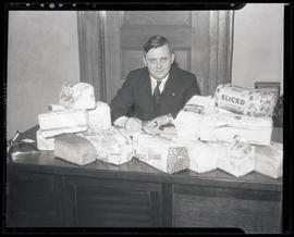 Joseph K. Carson seated at desk piled with loaves of bread