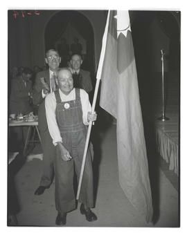 Unidentified man carrying flag at veterans club dinner