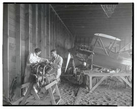 Two people in hangar, working on airplane engine