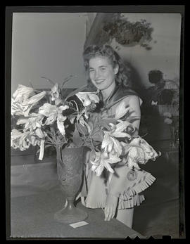 Costumed young woman posing with vase of lilies