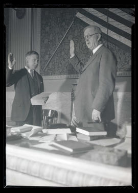 Hall S. Lusk administering oath to unidentified man