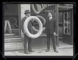 Barney Oldfield and unidentified man holding Oldfield tire