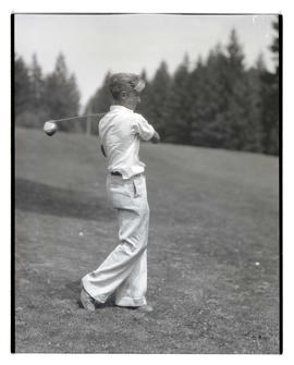 Young golfer posing with club