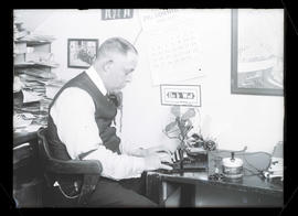 F. A. Lacy, Majestic Theater manager, at typewriter
