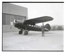 Unidentified man and airplane outside hangar