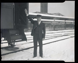 Joe Lochner, standing in snow next to train at Union Station