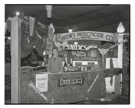Unidentified man at Snow's Insecticide Company booth, probably at Pacific International Livestock...
