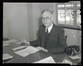 P. J. MacAuley of Meier & Frank, seated at desk