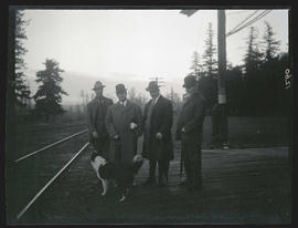 Group of men by railroad tracks
