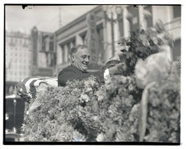 Franklin D. Roosevelt riding in flower-draped car, possibly during campaign stop in Seattle