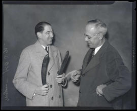 Myers of KOIN, holding pair of seed pods? and smiling at unidentified man