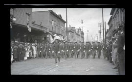 Men in uniform marching in parade, possibly in Astoria