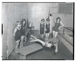 Unidentified girl demonstrating swimming technique as five others watch