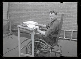 Unidentified man sitting in wheelchair and working at drafting table