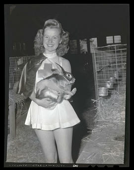 Costumed young woman holding rabbit