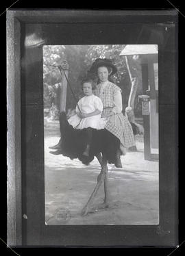 Photograph of two unidentified girls riding ostrich at Cawston Ostrich Farm, California