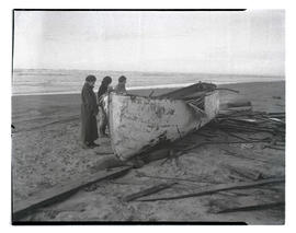 Three unidentified women looking at wrecked boat on beach