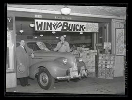 "Two men with car under ""Win this Buick"" sign at Piggly Wiggly store"