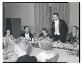 Unidentified man addressing fellow diners at formal event