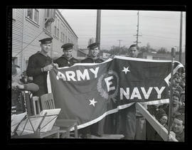 Three Navy servicemen and electrician Ed Mabie holding pennant during award ceremony at Albina En...
