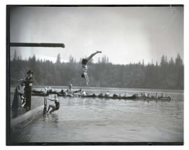 Diver in midair above river or lake