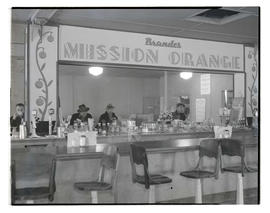 Four men at lunch counter with large sign for Brandes Mission Orange
