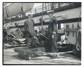 Commander Louis J. Gulliver and son looking at cannon aboard USS Constitution in Portland
