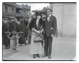 Unidentified woman and Charles P. Howard on sidewalk, full-length portrait