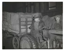 Postal worker on tractor, transporting sacks of mail