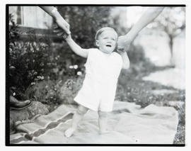 Baby outdoors, standing on blanket