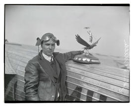 Pilot John H. Miller with trophy and airplane at Pearson Field
