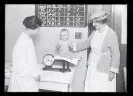Two women with baby being weighed during eugenics test?