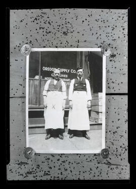 Photograph of two men outside Oregon Supply Company, Portland